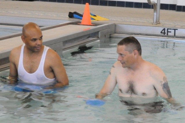 Sergeant 1st Class Nathan Bannerman, left, and Staff Sgt. Timothy Conley, talk during the Wounded Warrior Sports Program Monday at Tolson Youth Activities Center.  Aquatic therapy is designed to improve the strength, flexibility, endurance and socialization skills of wounded warriors.