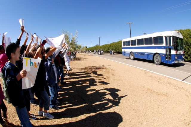 Students from Tiefort View Intermediate School, hold up a 'Thank You' signs while veterans from the Vietnam War pass in front of thier school on Fort Irwin, Calif., April 7. The veterans were on their way to the Fort Irwin Welcome Home Day Ceremony for Vietnam War veterans.