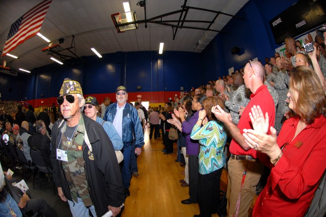Veterans from the Vietnam War enter the Freedom Fitness Gym on Fort Irwin, Calif., to applause and cheers from Soldiers and the Fort Irwin community, April 7.