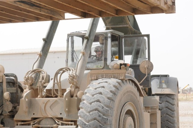 Spc. Christopher A. Ward, a Rough Terrain Container Handler operator with the 611th Seaport Operations Company out of Fort Eustis, Va., 541st Combat Sustainment Support Battalion, 15th Sustainment Brigade, 13th Sustainment Command (Expeditionary) and a Nampa, Idaho, native, waits to load a container onto a trailer as he operates the RT-240 Kalmar, April 3 at the container yard at Contingency Operating Base Speicher, Iraq.