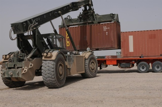 Soldiers with the 611th Seaport Operations Company out of Fort Eustis, Va., 541st Combat Sustainment Support Battalion, 15th Sustainment Brigade, 13th Sustainment Command (Expeditionary) operate the RT-240 Kalmar to unload a container from a trailer.