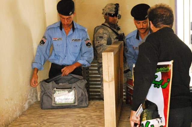 Iraqi border police check bags at the Shalamcha Port of Entry while Spc. Asher Hisaiah, 1st Battalion, 377th Field Artillery Regiment, 17th Fires Brigade, provides security, April 1, 2010.