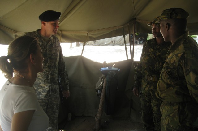 """Maj. Mbangwe, Ambassador Huddleston and Lieutenant Colonel Wyatt enjoy a light-hearted moment while listening to tales of camp life at a BDF field operating base in north eastern Botswana. Soldiers use the base camp to conduct patrols into the surrounding bush as part of the Government of Botswana's highly successful anti-poaching campaign. BDF soldiers frequently deploy around the country on """"real world"""" operations to defend the nation's sovereignty, protect its diverse and populous wildlife and support civil authorities."""