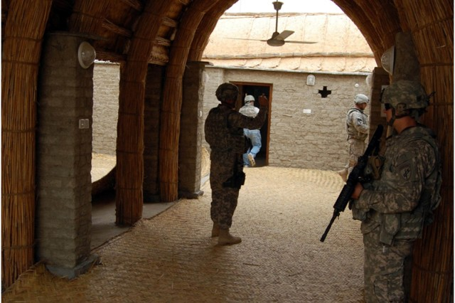 "Soldiers from Task Force Pathfinder's Personal Security Detachment secure the Adobe House during the project's final inspection March 1, 2010, in Al Chabayish.  The house is a blend of adobe and reed building materials used frequently by marsh Arabs in southeast Iraq. Construction of the ""model"" adobe house was coordinated with Task Force Pathfinder and the Dhi Qar Provincial Reconstruction Team."