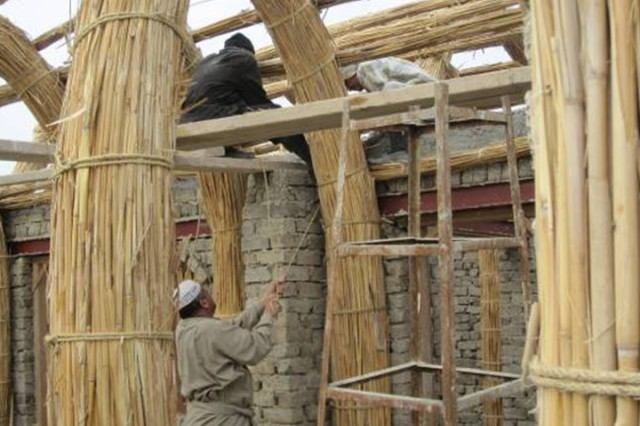 "Local contractors construct the main reed arches of a marsh Arab mudhif.  The house is a blend of adobe and reed building materials used frequently by marsh Arabs in southeast Iraq. Construction of the ""model"" adobe house was coordinated with Task Force Pathfinder and the Dhi Qar Provincial Reconstruction Team."
