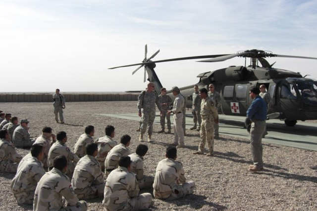 Salah, a senior Iraqi medic assigned to 2nd Commando Battalion, 11th Brigade, Iraqi Department of Border Enforcement, trains his peers on aerial evacuation with U.S. advisors from 4th Brigade Combat Team, 1st Armored Division at Joint Security Station Chilat, in northern Maysan Province, March 27, 2010.