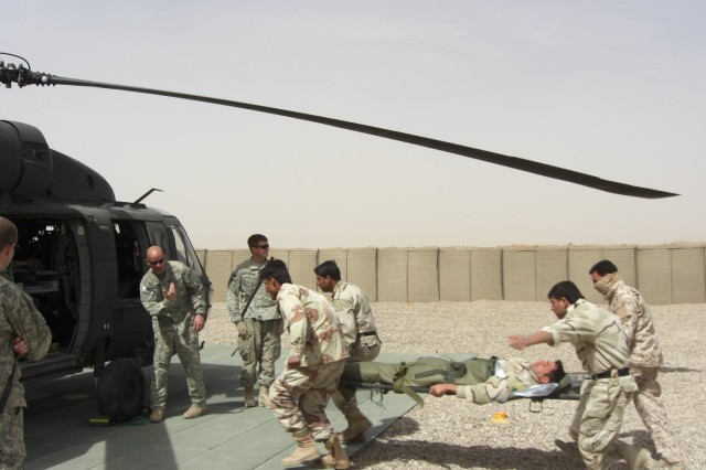 Sgt. Carey Atkins, a UH-60 Black Hawk crew chief assigned to Company C, 3rd Battalion, 238th Aviation Regiment, waves a Department of Border Enforcement litter team up to load a casualty.  The DBE is advised by Border Transition Team Phoenix, attached to 4th Brigade Combat Team, 1st Armored Division.