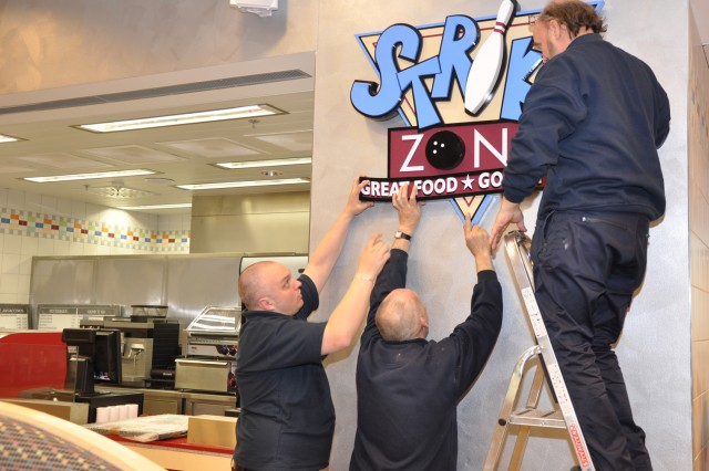 Workers hang up the Strike Zone sign in the new Wiesbaden Entertainment Center in preparation for the grand opening.