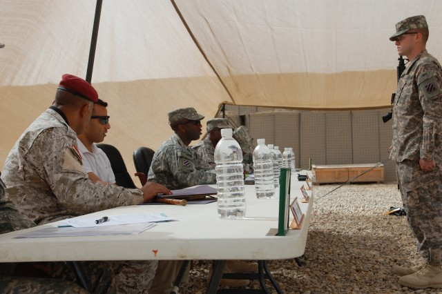 Private 1st Class John Young, Battery A, 1st Battalion, 10th Field Artillery Regiment, 3rd Heavy Brigade Combat Team, 3rd Infantry Division, of Marion, Ind., reports to the presidents of the board, Command Sgt. Maj. Mark A. Aaron, 1st Bn., 10th FAR, and Command Sgt. Maj. Abas Abad Al Hussain, 8th Iraqi Army Motorized Transportation Regiment, March 6, 2010, at Contingency Operating Base Delta, Iraq.