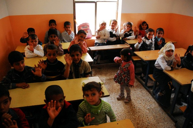 Children of the Ar'diyyat Primary School in Muthanna Province take their seats at new desks immediately after the conducting the ribbon cutting ceremony on February 17, 2010.