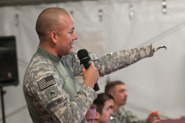 Retired Sgt. Juan Arredondo, an injured veteran, points to his brother at a town hall meeting with other Soldiers at Al Asad Air Base, Iraq. Arredondo, who lost an arm to an IED in 2005, is on tour with Operation Proper Exit, a program that allows wounded veterans to return to where they were injured to help find internal healing.