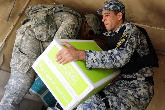 An Iraqi federal policeman and Sgt. Alexander Hudson of the 7th Cavalry Regiment, carry boxes of books for distribution at Ishtar Primary School, during a book drop conducted April 11.