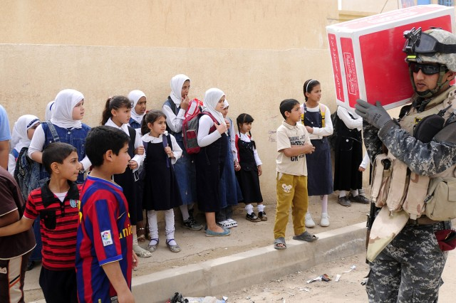 An Iraqi federal policeman carries boxes of books for distribution at Al Fursan Primary School during a book drop conducted by Iraqi Security Forces and Soldiers from the 7th Cavalry Regiment on April 11.