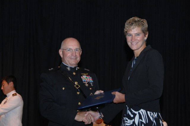 Beth A. Scherr, NPS MSCM curriculum graduate with distinction and Outstanding Thesis Award recipient for research work on a Joint Applied Project, receives her diploma from Conant at the September 2009 NPS graduation ceremony.