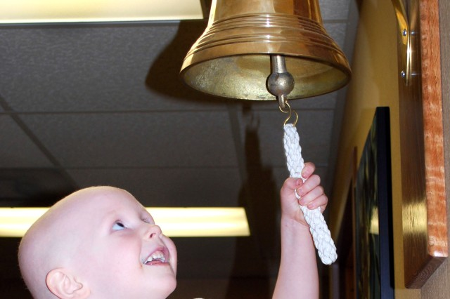 """Abigail Barrett, 4, rings the """"off-chemo"""" bell at Madigan Army Medical Center to celebrate the achievement of completing her chemotherapy treatments. The Pediatric Oncology Clinic treats about 40 patients, providing personalized attention with access to a physician 24 hours a day, seven days a week."""