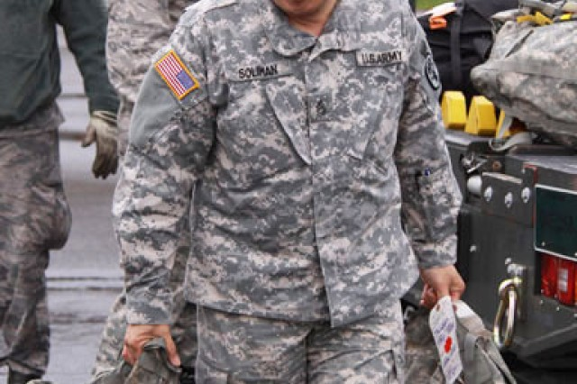 Sgt. 1st Class Noel Soliman carries patients' baggage from a medevac mission March 11 at McChord Field.