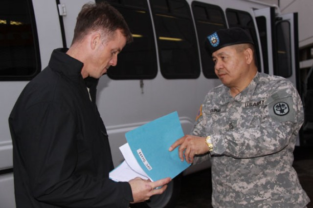 Sgt. 1st Class Noel Soliman ensures Sgt. 1st Class Christopher Scott receives his in-processing packet upon his arrival to the WTB.