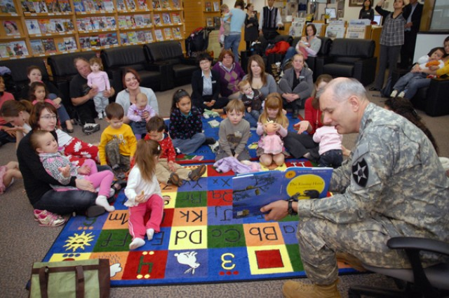 """Maj. Gen. Michael S. Tucker reads """"The Kissing Hand"""" by Audrey Penn to military children and Families during story time in Red Cloud Garrison's Library April 6."""