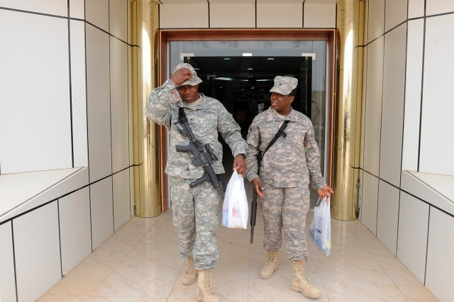 BAGHDAD - Sgt. 1st Class Shaheed Shakir, a liaison officer for 1st Advise and Assist Brigade, 82nd Airborne Division, and his daughter, Sgt. Siobhan Eastman, the supply sergeant with Company B, 37th Engineer Battalion, 20th Engineer Brigade, 18th Airborne Division, exit the new shopping center at Camp Liberty April 8. Eastman is currently stationed at Joint Air Base Balad but went to Liberty on a supply mission where she was able to reunite with her father. (U.S. Army photo by Sgt. Samantha Beuterbaugh, 366th MPAD, USD-C)