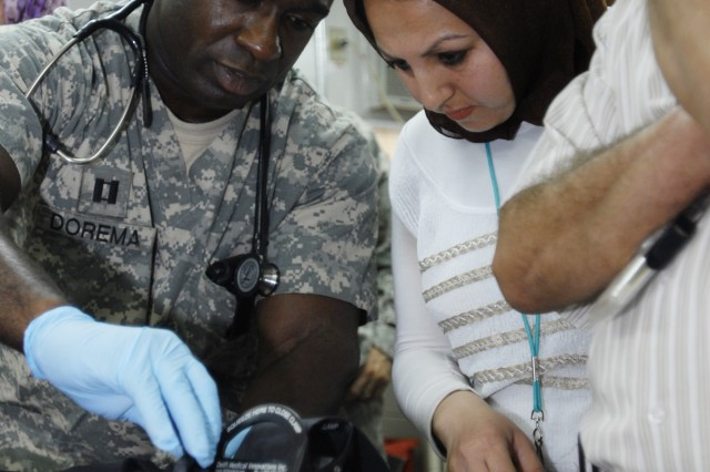 Capt. Ernest Dorema, an officer in charge of the emergency room at the 28th Combat Support Hospital and a Palm Beach, Fla., native, shows Sinna Abdul Azeez, an anesthesiologist with Yarmouk Hospital, how to use a Combat Application Tourniquet on the leg of a mock casualty during an exercise as a part of Operation Medical Alliance held at Sather Air Base, April 7. Sinna, and several other doctors from Yarmouk Hospital, visited 28th CSH for the first time to observe standard operating procedures of the hospital.