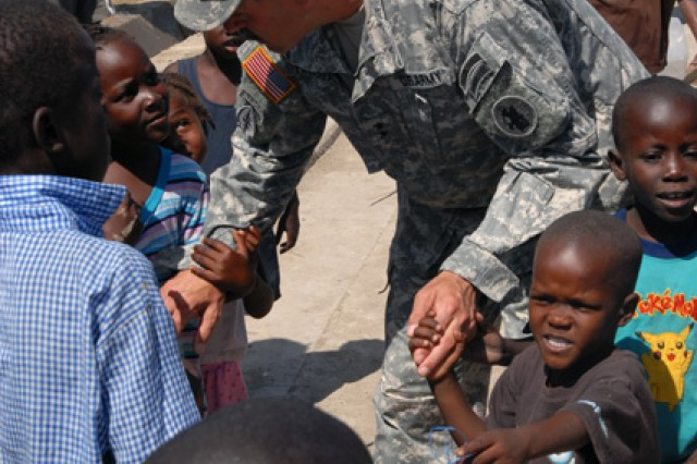PORT-AU-PRINCE, Haiti- Maj. Gen. Simeon Trombitas, deputy commanding general, JTF-Haiti, holds hands with some children at an internally displaced personnel camp on March 21. Trombitas took some time to talk with local nationals and see how they were living in the camps. He also introduced himself to the children and spent a moment getting to know them. (U.S. Army photo by Pvt. Samantha D. Hall/11th PAD)