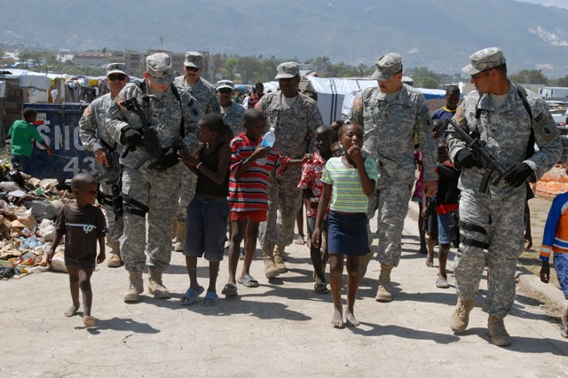 PORT-AU-PRINCE, Haiti- Maj. Gen. Simeon Trombitas, deputy commanding general, JTF-Haiti, and fellow soldiers walk through an internally displaced personnel camp March 21. Trombitas took some time to say hello to the children and other Haitians living in the camp. (U.S. Army photo by Pvt. Samantha D. Hall/11th PAD)