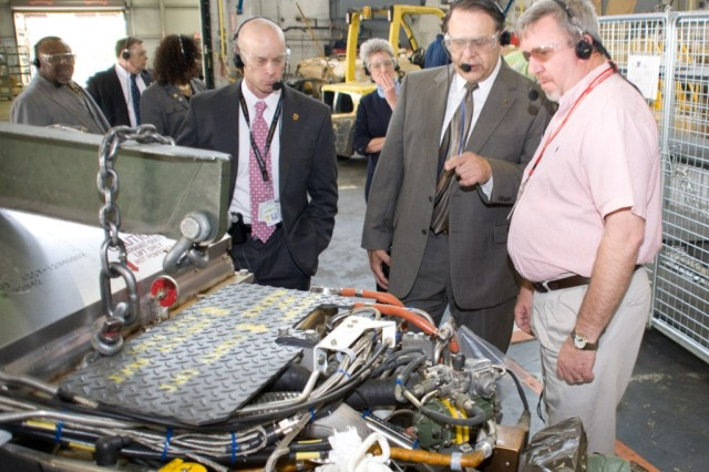 Chuck Gunnels, right, explains the powerpack assembly process to Davis Tindoll Jr., center, southeast director of Installation Management Command, in Anniston Army Depot's combat vehicle disassembly/reassembly building. Tindoll was accompanied by Phillip Trued and other IMCOM associates.