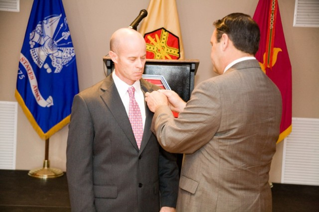 Davis Tindoll Jr., southeast director of Installation Management Command, places the IMCOM organizational pin on Phillip Trued, who was named Anniston's garrison manager during the April 7 ceremony.