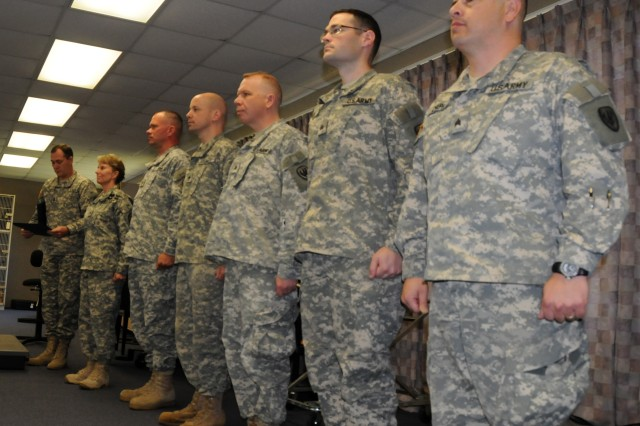 Crossfire members prepare to receive certificates from Garrison Command Sgt. Maj. Dwaine Walters, far left, and Garrison Commander Col. Yvette Kelley, second from left, April 12 at Bldg. 6902.