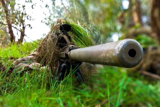 After crawling through grass and brush toward their target, a sniper team from HHC, 1/36 Inf., 2nd HBCt, 3rd ID, set their sights on their target during a two-week training school where U.S. Soldiers trained Iraqi Army Special Forces at the Al Kindi Iraqi Army base in Mosul, Iraq.