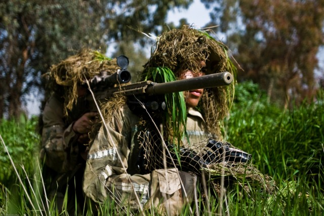 """Using tall grass for cover, a Soldier from Headquarters and Headquarters Company, 1st Battalion, 36th Infantry Regiment, 2nd Heavy Brigade Combat Team, 3rd Infantry Division, sets up his shot using the """"buddy-supported"""" firing postion, taking aim with his M110 Sniper Rifle. The snipers trained Iraqi Army Special Forces soldiers as part of a two-week sniper training course in Mosul, Iraq."""
