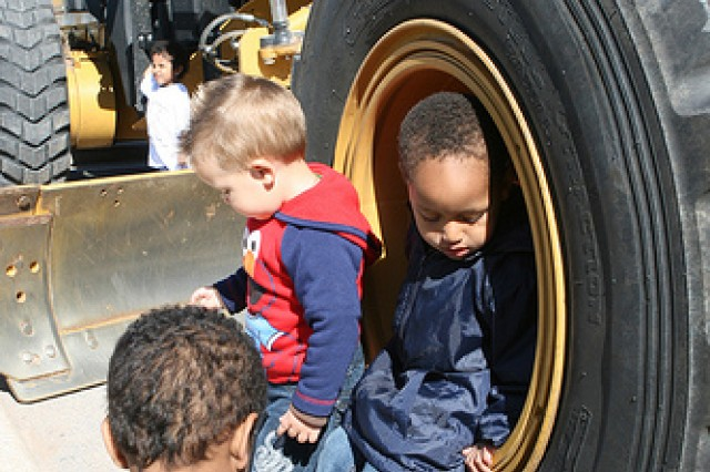 Jose Montero and Ethan Dixson, both with a Family Child Care provider, explore the wheel of a tractor during Wheels Day April 8 in the parking lot of Tincher Child Development Center at Fort Sill. Wheels Day offered children an opportunity to see, touch and climb on wheeled vehicles of all kinds.