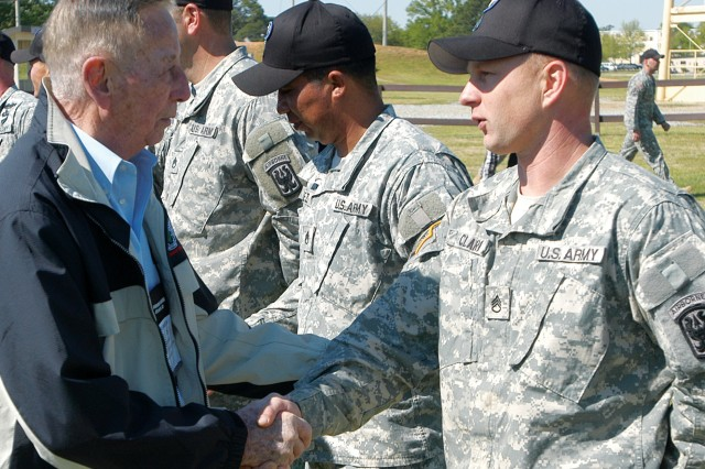 LTG(R) Richard Seitz, a World War II veteran who commanded the Airborne School from 1950 to 1953, shakes hands with SSG Kristopher Clark, a black hat with C Company, 1st Battalion (Airborne), 507th Parachute Infantry Regiment.