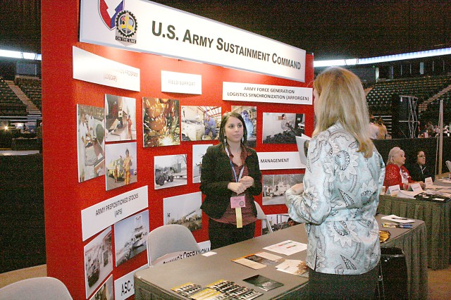 Danielle Toste, an Army intern representing Headquarters, Army Sustainment Command, helps an attendee at the 2010 Midwest Small Business Government Contracting Symposium held April 12-13 in Moline, Ill., at the i Wireless Center.