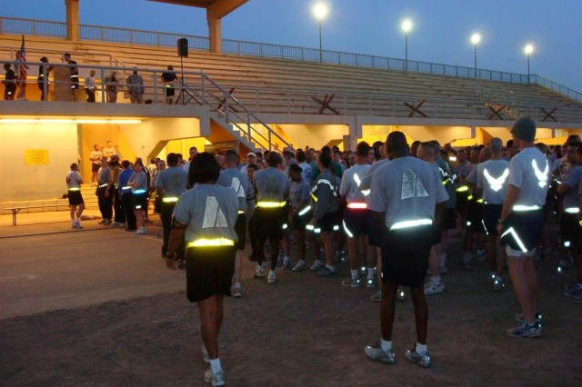 Service members stand at the starting line April 9 at Holt Stadium at Joint Base Balad, Iraq, awaiting the start of the Sexual Assault Awareness Month 5K run.