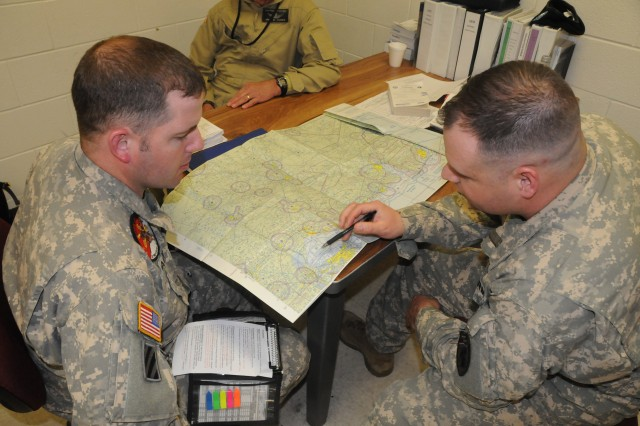 CW3 Keith Lacy and CW4 Matt Stewart discuss maps in the Rotary Wing Instrument Flight Examiners Course at Fort Rucker. Through a combined effort between 1st Bn., 223rd Avn. Regt., 110th Avn. Bde. and LSSI contractors, Global Positioning System training was added to the course recently.