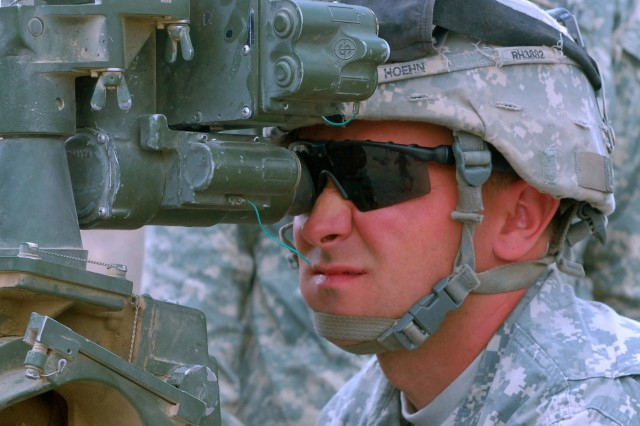 Sgt. Rolla Hoehn, a gunner for B battery, 4-25th Artillery, peers through the viewfinder of the M-119A2 howitzer to check his sight picture in preparation for a firing mission in June 2009 in Afghanistan. Although the battery performed numerous maneuver operations, they still found time to maintain their proficiency with their artillery weaponry.