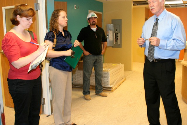 Mary Beth Smith and Heather Sapp listen to Don Hulst, operations coordinator for Child, Youth and School Services, as they tour what will be the reception area of the new Child Development Center, located behind the FMWR Fitness Center.