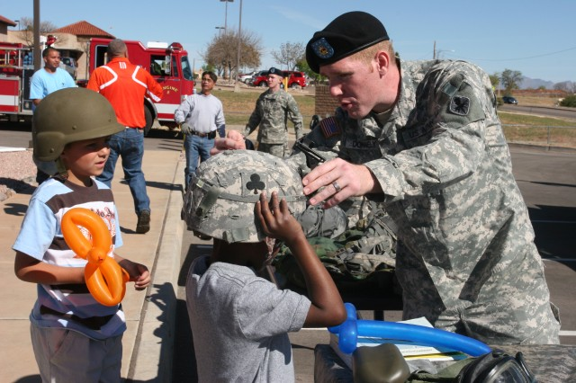 Pvt. Merrick Donnelly, Headquarters, Headquarters Company, U. S. Army Intelligence Center of Excellence assists Wellington Jones in trying on Army gear, and Austin Vail watches as Jones is suited up.  Both boys are taking part in Saturday's Month of the Military Child Celebration in conjunction with the grand opening of the new Child Development Center on Fort Huachuca.