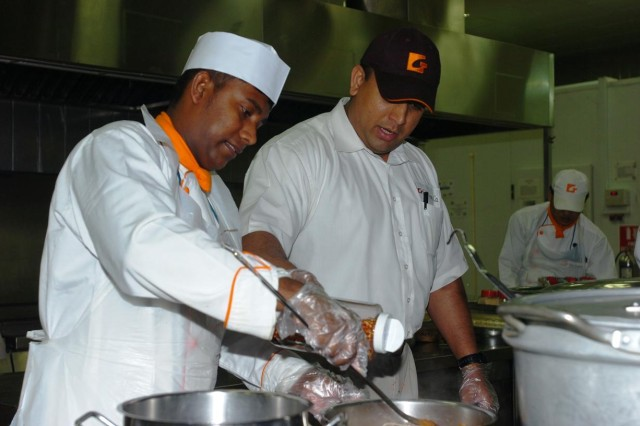 Mr. Keith Wijeratna (pictured left), a Sri Lanka native and South DFAC location manager, Gulf Catering Company, works with one of his subcontractors to properly spice a dinner dish March 27, at the Contingency Operating Base Speicher South Dining Facility, the largest dining facility at COB Speicher, near Tikrit, Iraq. Mr. Wijeratna supervises the contracting staff engaged in preparing and serving food in accordance with applicable health and safety standards, and is responsible for aspects of DFAC administration, cost management, safety management and staff training programs.