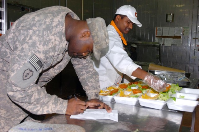 "Private Reginald Nelson, food service specialist, 209th Aviation Support Battalion, 25th Combat Aviation Brigade, Task Force Wings, confirms the quantity of ""to-go"" plates March 16, to be delivered to Soldiers unable to leave their work at the South Dining Facility, the largest dining facility at Contingency Operating Base Speicher, near Tikrit, Iraq."