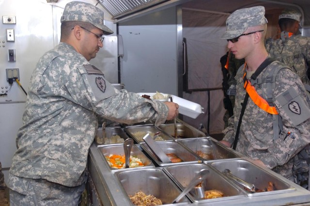 Specialist Stephen Villanueva (pictured left), food service specialist, 209th Aviation Support Battalion, 25th Combat Aviation Brigade, Task Force Wings, serves a Soldier dinner at the Lobos Grill, one of five remote TF Wings dining locations at Contingency Operating Base Speicher, near Tikrit, Iraq.