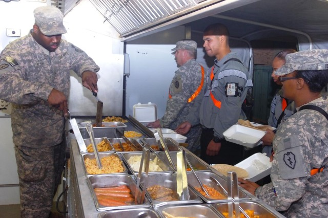 "Private Reginald Nelson (pictured left), food service specialist, 209th Aviation Support Battalion, 25th Combat Aviation Brigade, Task Force Wings, serves Soldiers quesadillas at the ""Lobos Grill,"" one of five remote TF Wings dining locations at Contingency Operating Base Speicher, near Tikrit, Iraq."