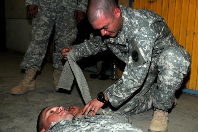 Sgt. Kevin W. Barton, a gunner with G Troop, 2nd Squadron, 278th Armored Cavalry Regiment, 13th Sustainment Command (Expeditionary) and an Ashland City, Tenn., native, practices the application of a pressure dressing on fellow student Sgt. Ryan M. Williams, a gunner with G Troop, 2/278th ACR and an Ashland City, Tenn., native, April 12 during the combat lifesaver course at the 278th ACR headquarters building at Joint Base Balad, Iraq.