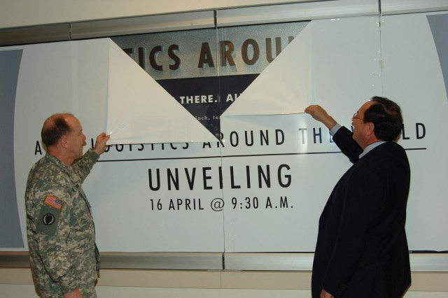 "Lt. Gen. Mitchell H. Stevenson, Deputy Chief of Staff of the Army for Logistics (left) and Mr. Doug Wilson, Assistant Secretary of Defense for Public Affairs (right), peel back the cover of the ""Army Logistics Around the World"" display during the April 16, 2010 unveiling ceremony in the Pentagon.  Using six TV screens, ""Army Logistics Around the World"" proudly displays candid images of Logisticians performing their many duties all over the world."