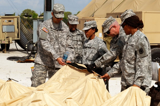 FORT HOOD, Texas-Soldiers from the 41st Fires Brigade examine the sides and Velcro of the new deployable rapid assembly shelter (DRASH) system, April 14. The new DRASH system will be used for field operations and the Soldiers are scheduled to validate training on it throughout May and June.