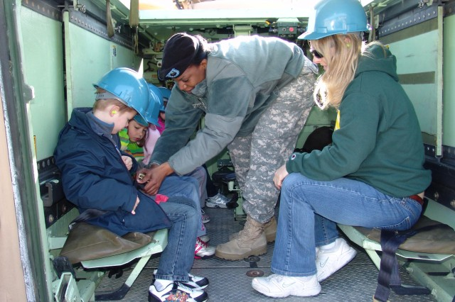 Master. Sgt. Angela Chappell, 3/405th Army Field Support Brigade, ensures the visiting students from Livorno Unit Elementary School have their seatbelts properly fastened before going on a ride in a military vehicle.