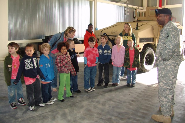 Staff Sgt. Stephen Walker, 3/405th Army Field Support Brigade, answers question about his job during a visit from students from Livorno Unit Elementary School.