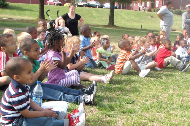 """Children clap after one of McMahan's performances. McMahan used magic tricks, clown antics and props to entertain the children. He also let the children participate in the show by using their fingers as magic wands and letting them say  """"magic words."""""""