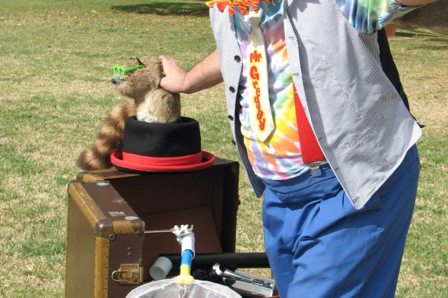 """Family entertainment specialist Greg McMahan, who goes by the stage name Mr. Greggy, prepares for one of his biggest tricks Aca,!"""" having his his Aca,!A""""pet racoonAca,!A? Rocky jump through a ring of fire and land safely in the net."""
